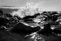 Caucasian young adult woman lying nude in tidal pool with wave crashing in distance