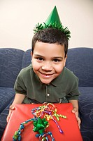Hispanic boy wearing party hat holding large birthday present smiling and looking at viewer