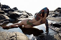 Sexy nude tattooed Caucasian woman lying in tidal pool
