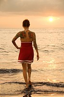 Attractive tattooed Caucasian woman on beach at sunset