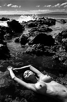 Filipino young nude woman lying on back in water on rocky beach with eyes closed and arms stretched over head