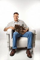 Mid_adult Caucasian man sitting holding Persian cat