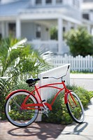 Red beach cruiser bicycle propped against fence in front of house