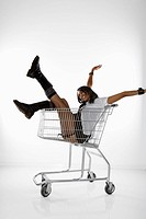 Mid_adult African American woman in mini skirt and boots sitting in shopping cart with arms and legs out
