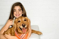 Female adolescent Caucasian holding Golden Retriever dog