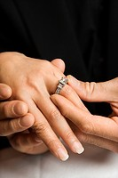 Prime adult Asian male putting engagement ring on female's hand