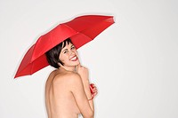 Shirtless young Caucasian woman smiling at viewer and holding red umbrella