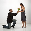 African American mid adult man on knees giving woman bouquet of flowers