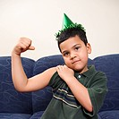 Hispanic boy wearing party hat playfully flexing arm muscle while looking at viewer