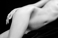 Selective focus of Caucasian mid adult female nude body lying on side