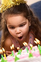 Hispanic girl wearing party hat blowing out candles on birthday cake