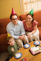 Caucasian boy and parents in party hats eating birthday cake