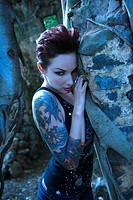 Blue_toned portrait of fearful looking tattooed Caucasian woman next to concrete wall
