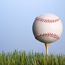 Studio shot of baseball resting on golf tee in grass