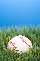 Studio shot of baseball resting in grass