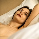 Nude Caucasian mid_adult woman relaxing in bed