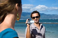 Mid_adult Caucasian man on beach pointing video camera at woman