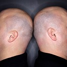 Close up of Caucasian mid adult identical twin bald men standing back to back