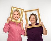 Caucasian middle aged woman and senior woman holding picture frames over faces