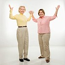 Caucasian senior woman and middle aged woman with arms in air