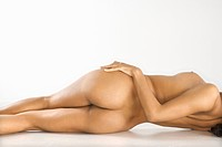 Back view of attractive nude woman lying on floor against white background