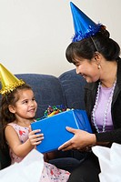 Mother giving daughter present at birthday party