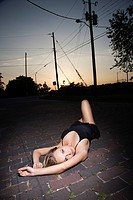 Caucasian mid-adult blonde woman wearing little black dress lying in street at sunset (thumbnail)