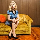 Attractive Caucasian woman sitting on retro style couch (thumbnail)