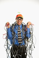 African American businessman wrapped in computer cables wearing nerd hat and glasses