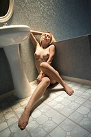 Attractive nude young adult Caucasian blond woman sitting on bathroom floor