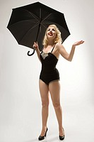Attractive Caucasian woman wearing retro swimsuit in pinup pose with umbrella (thumbnail)