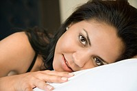 Portrait of Hispanic young adult woman lying down