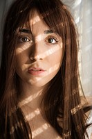 Portrait of pretty Caucasian young woman with sunlight through window
