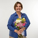 Caucasian middle aged woman holding bouquet of flowers and smiling at viewer