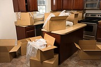 Cardboard moving boxes with bubble wrap in kitchen
