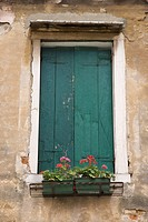 Window with closed shutters and flowerbox in Venice, Italy