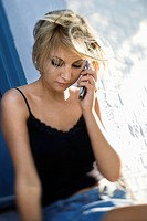 Caucasian mid_adult blonde woman sitting against building talking on cell phone looking down
