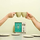 Caucasian male and female hands toasting with coffee cups across retro kitchen table setting