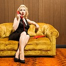 Attractive Caucasian woman talking on red retro phone