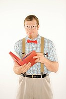 Caucasian young man dressed like nerd with book open looking at viewer