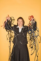 Caucasian businesswoman smiling holding pile of tangled cords and wires