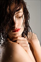 Portrait of bare attractive Caucasian redhead young woman with wet hair and skin