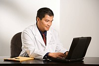 Asian American male doctor sitting at desk with charts typing on laptop computer