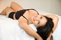 Hispanic young adult woman lying on bed wearing lingerie and looking at viewer