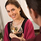 Mid adult Caucasian couple smiling and toasting wine glasses