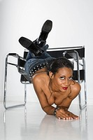 Topless mid_adult Afican American woman sliding off chair towards viewer