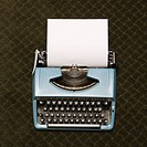 Vintage blue typewriter on green carpet