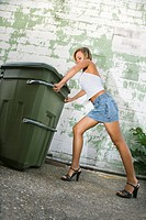 Caucasian mid_adult blonde woman wearing mini skirt and heels pushing trash can in alley