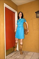Caucasian young adult woman in retro clothing standing beside doorway