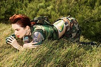 Tattooed woman in camouflage lying on grass looking through binoculars